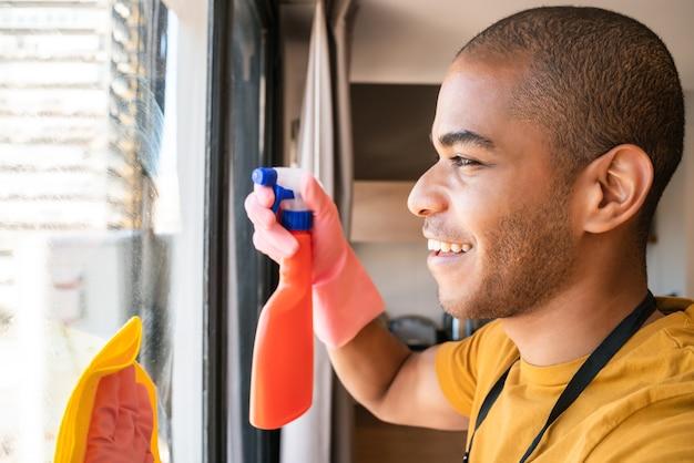 Retrato de jovem governanta limpando a janela de vidro em casa. conceito de arrumação e limpeza.