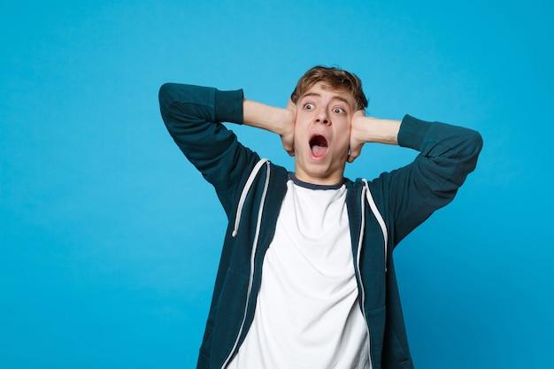 Retrato de jovem gritando chocado em roupas casuais, olhando de lado, cobrindo as orelhas com as mãos isoladas em azul.