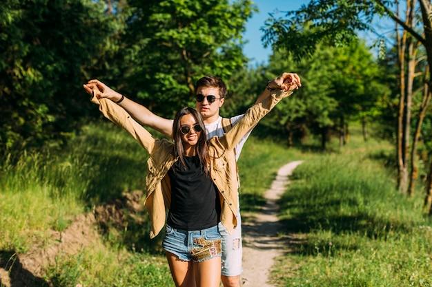 Retrato, de, jovem, hiking, par, outstretching, seu, mãos