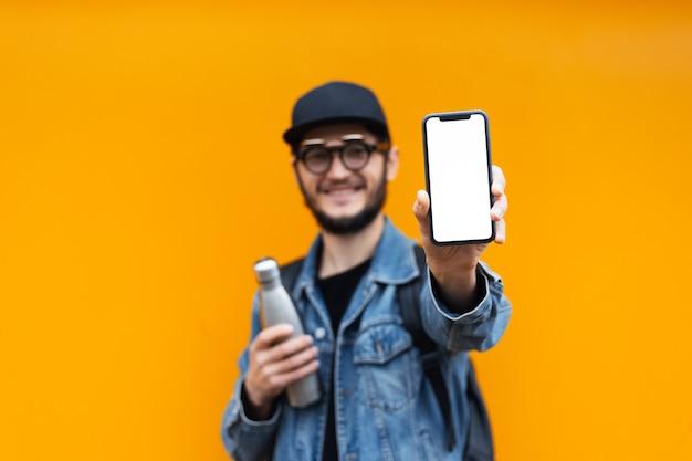 Retrato de jovem hippie alegre, segurando a garrafa de aço thermo eco para água e smartphone com maquete branca, na parede amarela ou laranja.