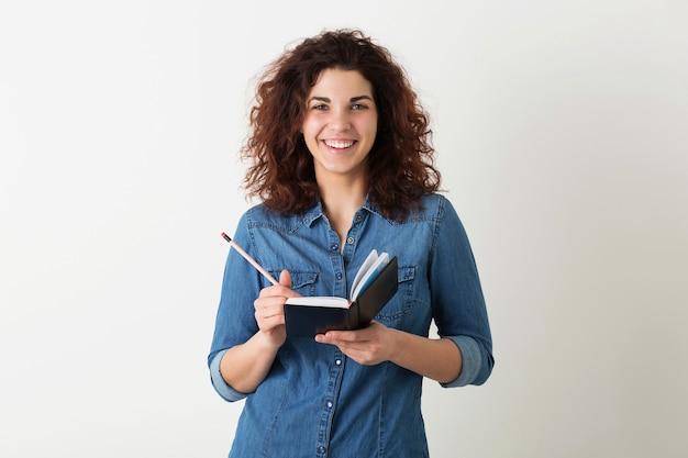 Retrato de jovem hippie natural sorrindo linda mulher com penteado encaracolado em camisa jeans, posando com caderno e caneta isolado no fundo branco do estúdio.