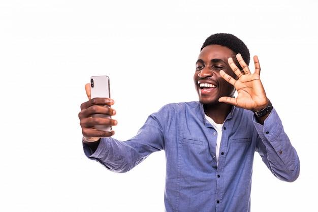 Retrato de jovem homem afro-americano bonito usando o smartphone para tirar fotos de selfie e sorrindo em pé contra a parede branca