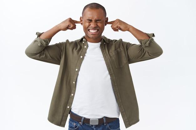 Retrato de jovem homem afro-americano irritado com roupas casuais, cansado de o vizinho falar muito alto