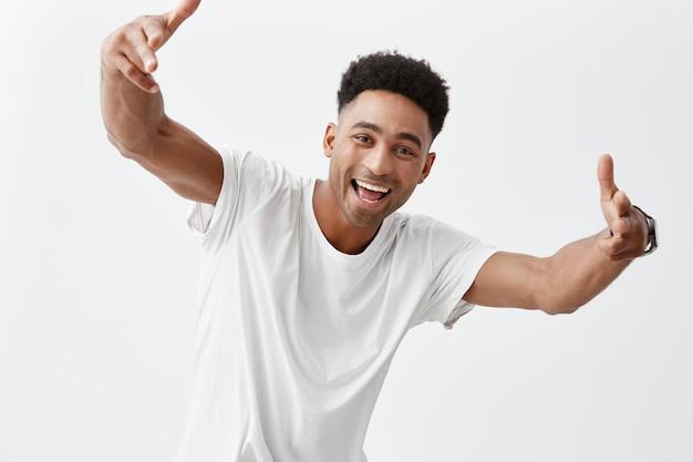 Retrato de jovem homem atraente de pele escura com penteado afro em camiseta casual branca, sorrindo com dentes, gesticulando com as mãos na câmera, olhando na câmera com expressão feliz e animada