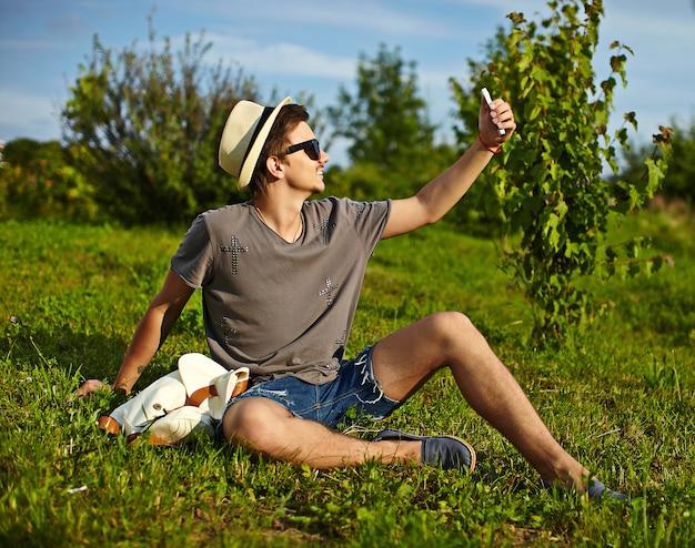 Retrato de jovem homem atraente moderno e elegante em pano casual no chapéu em copos sentado no parque na grama verde, fazendo selfie