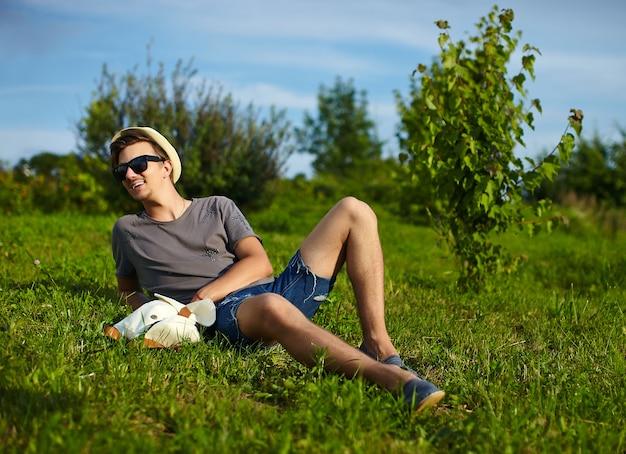 Retrato de jovem homem atraente moderno e elegante em pano casual no chapéu em copos sentado no parque na grama verde