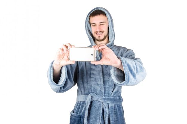 Retrato de jovem homem barbudo caucasiano em roupão azul leva selfie com smartphone isolado