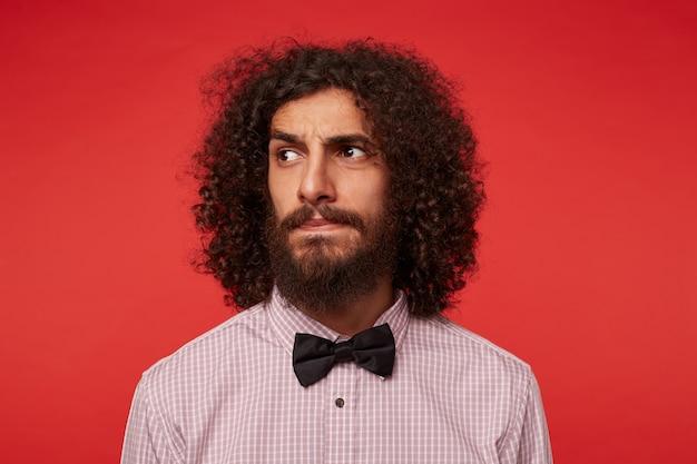Retrato de jovem homem barbudo encaracolado de cabelos escuros levantando as sobrancelhas e mantendo os lábios dobrados enquanto olha seriamente para o lado, vestido com roupas formais