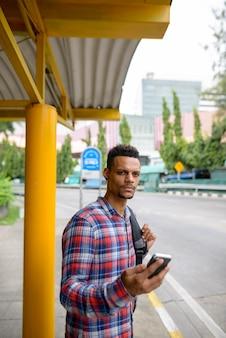 Retrato de jovem homem barbudo hipster africano como turista com mochila esperando no ponto de ônibus ao ar livre