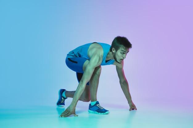 Retrato de jovem homem caucasiano ativo correndo, correndo no fundo do estúdio gradiente em luz de néon. treinamento de desportista profissional em ação e movimento. esporte, bem-estar, atividade, conceito de vitalidade.