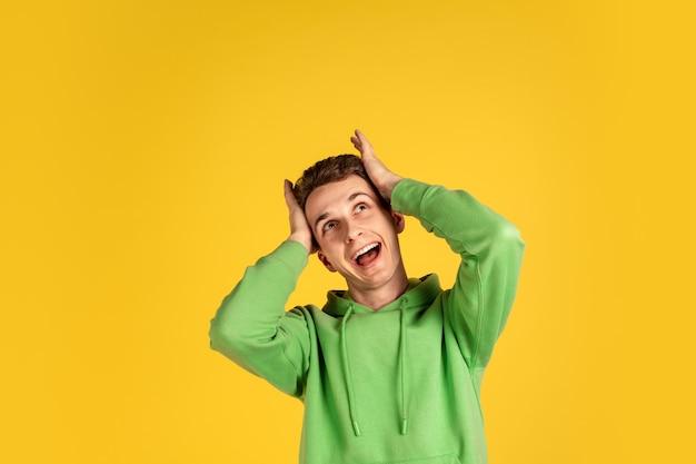 Retrato de jovem homem caucasiano isolado no fundo amarelo do estúdio