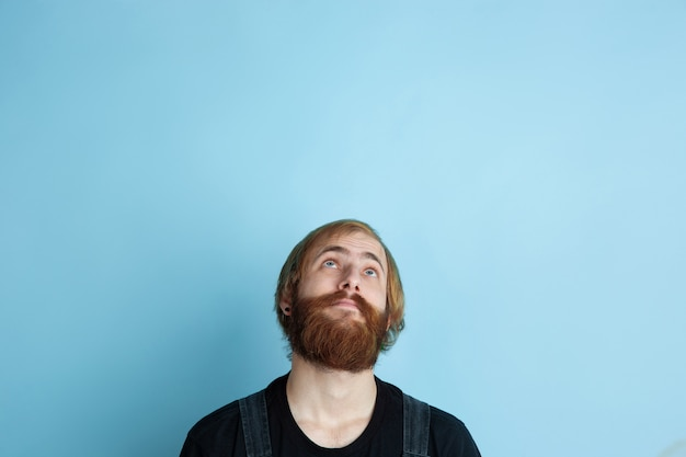 Retrato de jovem homem caucasiano parece sonhador, bonito e feliz. olhando para cima e pensando no espaço azul