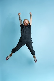 Retrato de jovem homem caucasiano parece sonhador, bonito e feliz. pulando. rindo sobre fundo azul do estúdio. copyspace para sua publicidade. conceito de futuro, alvo, sonhos, visualização.