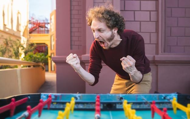 Retrato de jovem homem caucasiano se divertindo e jogando futebol de mesa.