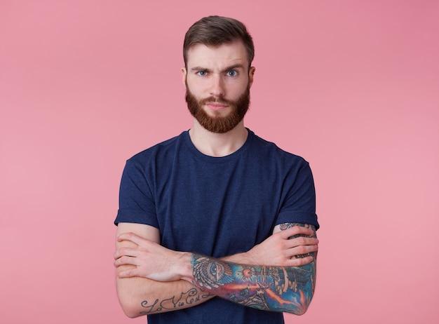 Retrato de jovem homem cheio de barba vermelha descontente com os braços cruzados, parece indignado, olhando para a câmera com a sobrancelha levantada, isolado sobre o fundo rosa.