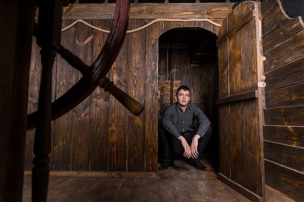 Retrato de jovem homem de negócios bem vestido e sentado no chão em uma porta aberta de um antigo navio à vela de madeira, levando para o interior dos aposentos e área de cabine