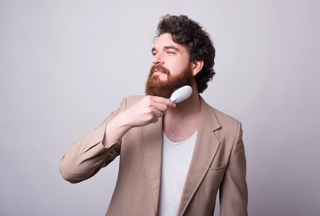 Retrato de jovem homem de terno em pé sobre uma parede branca e pentear a barba