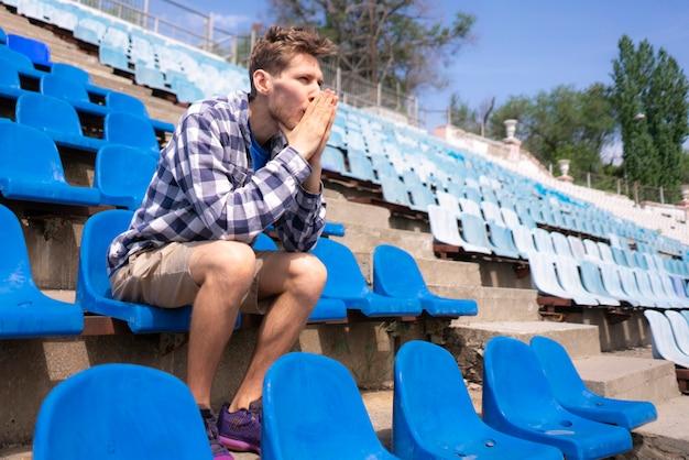 Retrato de jovem homem emocional sentado no estádio esportivo durante eventos de partida