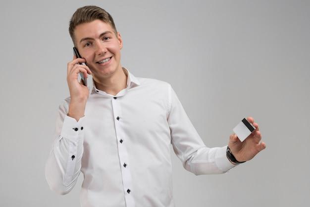 Retrato de jovem homem falando no celular com cartão de crédito na mão isolado no branco