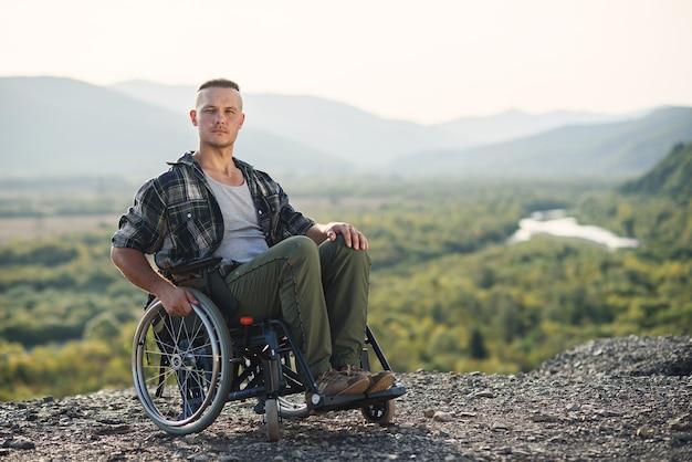 Retrato de jovem homem forte e motivado em uma cadeira de rodas, apreciando a beleza da natureza no