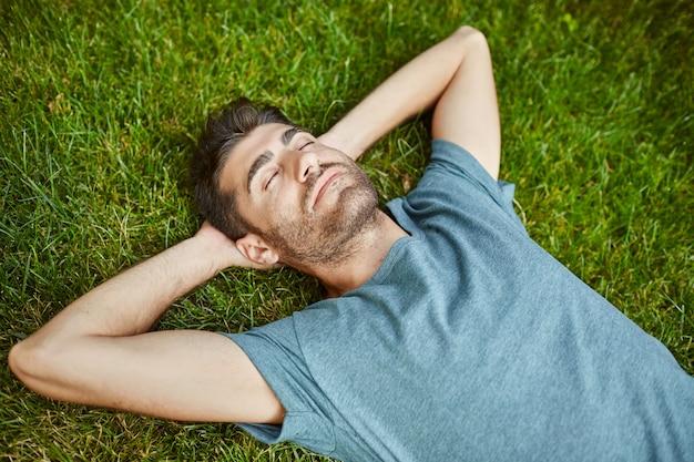 Retrato de jovem homem maduro de boa aparência caucasiano em pacífico camisa azul deitado na grama com sim fechado.