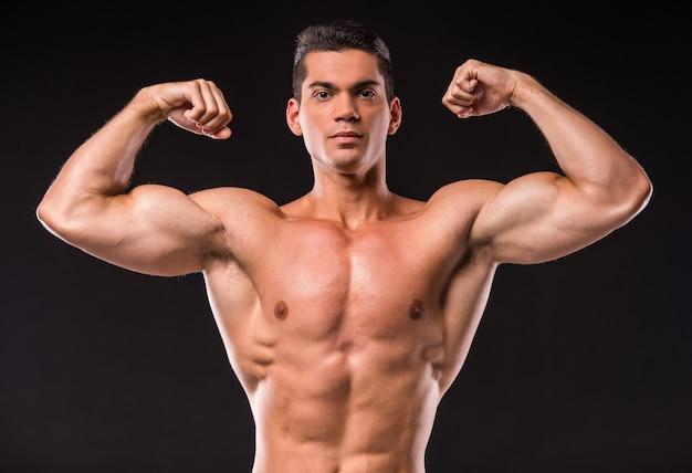 Retrato de jovem homem musculoso está flexionando seus músculos.