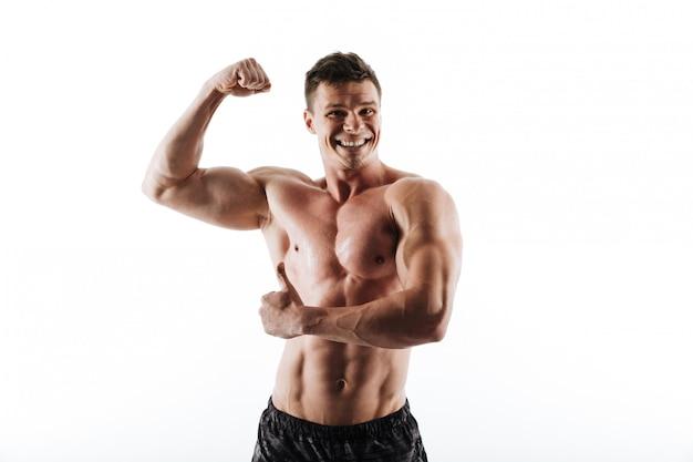 Retrato de jovem homem musculoso rindo mostrando seus bíceps e polegar para cima gesto