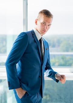 Retrato, de, jovem, homem negócios fica, perto, a, janela, com, passe bolso