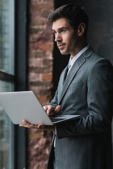 Retrato, de, jovem, homem negócios fica, perto, a, janela, usando computador portátil