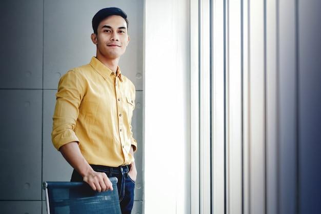 Retrato, de, jovem, homem negócios fica, por, a, janela, em, escritório
