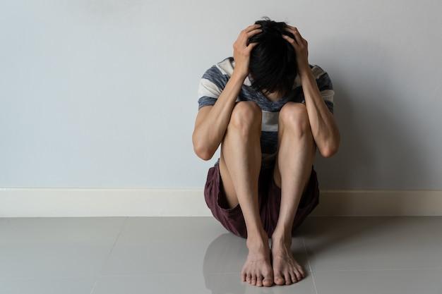 Retrato de jovem homem que sofre de depressão sente-se no chão