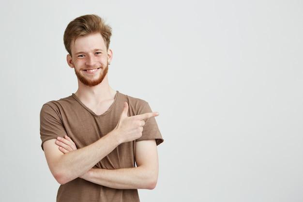 Retrato de jovem homem sincero bonito com barba sorrindo apontando o dedo no lado.