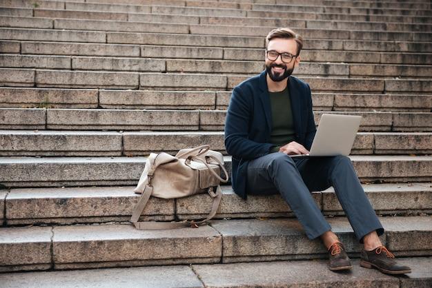 Retrato, de, jovem, homem sorridente, usando computador portátil