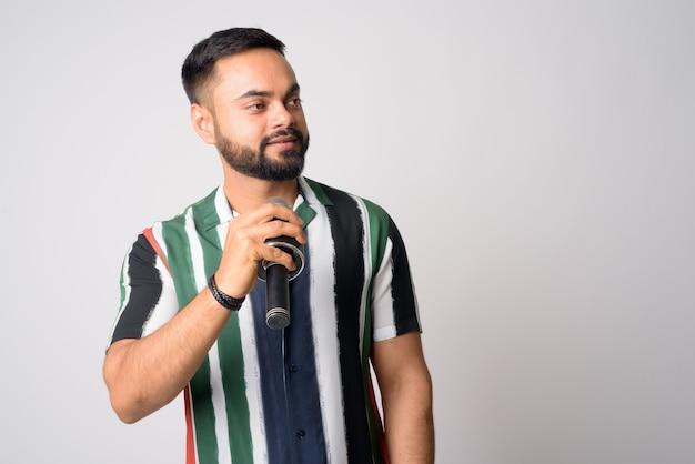 Retrato de jovem indiano barbudo bonito contra uma parede branca