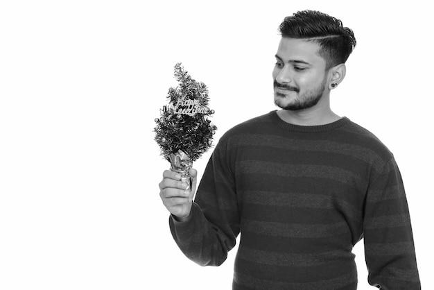 Retrato de jovem indiano barbudo bonito pronto para a véspera de ano novo em branco em preto e branco