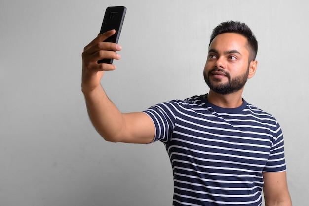 Retrato de jovem indiano barbudo em branco