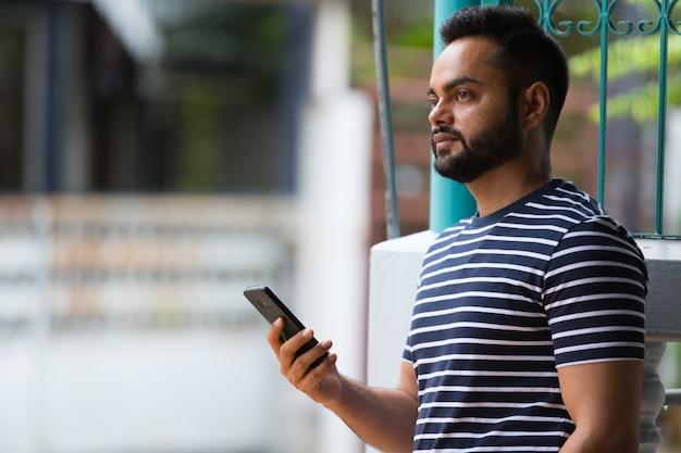 Retrato de jovem indiano barbudo na rua ao ar livre