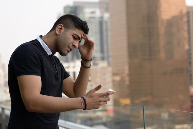 Retrato de jovem indiano bonito contra a vista da cidade