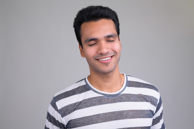 Retrato de jovem indiano bonito em branco