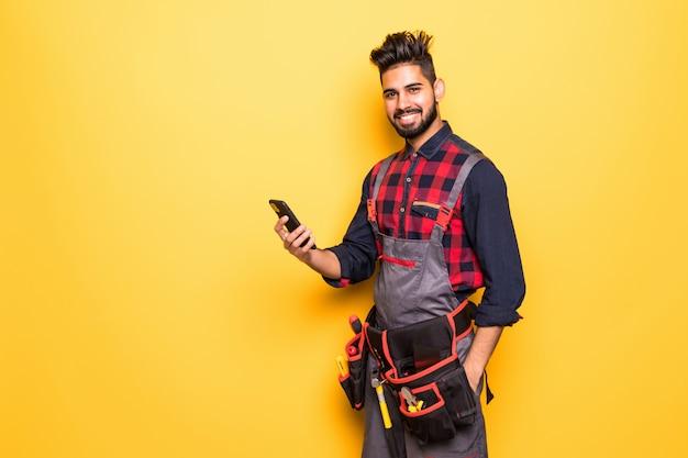 Retrato de jovem indiano masculino trabalhador da construção civil com telefone inteligente, vestindo roupas de proteção com cinto de ferramentas isolado em espaço amarelo