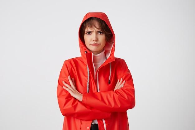 Retrato de jovem infeliz com o tempo chuvoso simpática senhora de cabelos curtos vestida com capa de chuva vermelha, com um capuz na cabeça, olhando para longe com expressão triste, em pé.