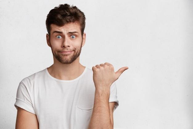 Retrato de jovem infeliz sente perplexidade e surpresa com olhos esbugalhados, tem olhar atraente, indica com o polegar um espaço em branco para o seu anúncio, texto promocional ou ouvinte.