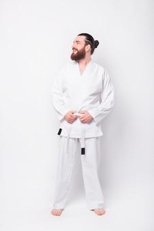 Retrato de jovem instrutor vestindo uniforme de taekwondo sorrindo e olhando para o lado
