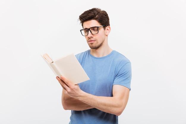 Retrato de jovem inteligente na camisa azul, usando óculos, lendo o livro com concentração, isolado sobre a parede branca