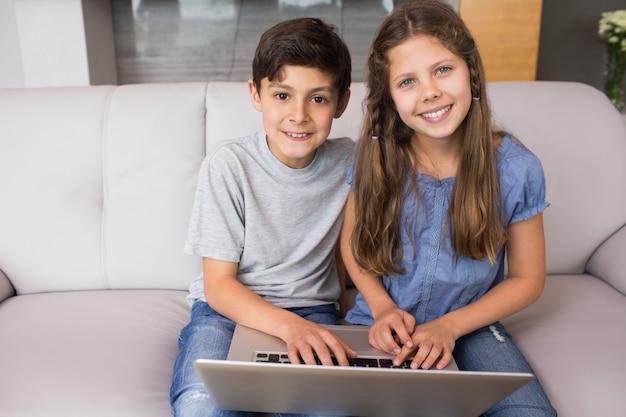 Retrato, de, jovem, irmãos, usando computador portátil, em, a, sala de estar