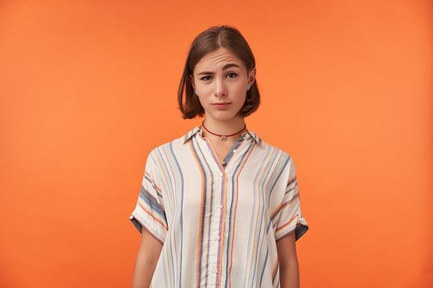 Retrato de jovem isolado contra uma parede laranja, olhando para você com uma sobrancelha levantada, vestindo camisa listrada. quando você ouve algo estranho.