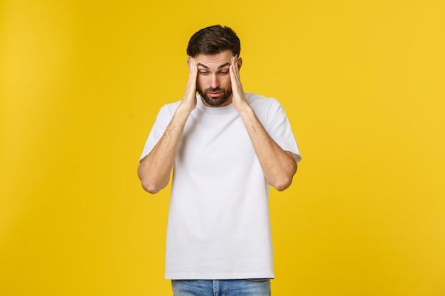Retrato de jovem isolado na parede amarela, sofrendo de dor de cabeça severa, pressionando os dedos nas têmporas, fechando os olhos para aliviar a dor