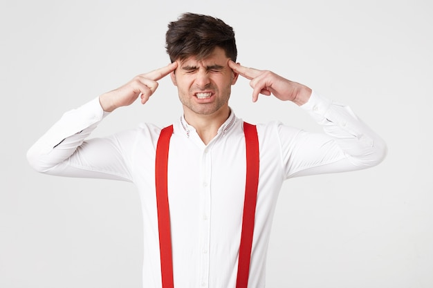 Retrato de jovem isolado no fundo branco, sofrendo de fortes dores de cabeça