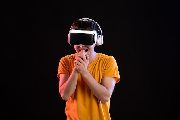 Retrato de jovem jogando videogame em fones de ouvido no piso escuro para videogame visual d tech