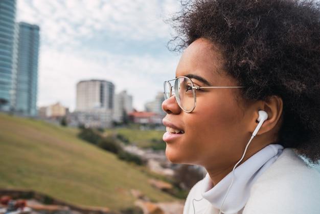 Retrato de jovem latina aproveitando o tempo livre e ouvindo música com fones de ouvido ao ar livre
